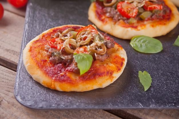 Selbst gemachte minipizza auf schwarzem