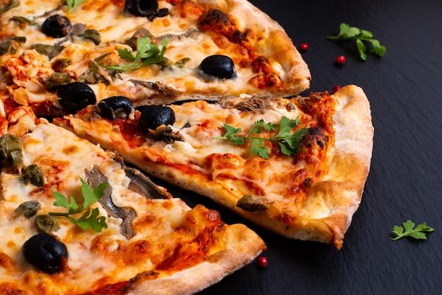 Selbst gemachte napoli pizza oder sardellenpizza auf schwarzem schieferstein