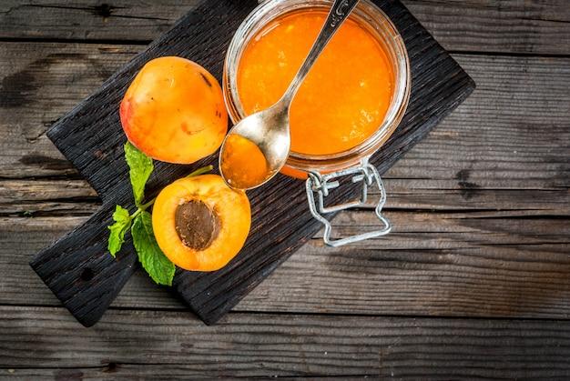 Selbst gemachte organische aprikosenmarmelade in den kleinen gläsern, auf einem rustikalen alten holztisch, mit aprikosen und tadellosen blättern