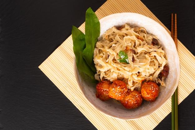 Selbst gemachte orientalische eiernudeln des asiatischen lebensmittelkonzeptes und würzige fleischklöschen in der keramischen schüssel auf schwarzem hintergrund