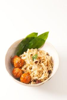 Selbst gemachte orientalische eiernudeln des asiatischen lebensmittelkonzeptes und würzige fleischklöschen in der keramischen schüssel auf weißem hintergrund