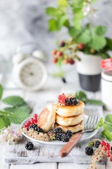 Selbst gemachte pfannkuchen mit beeren, den brombeeren, dem honig auf der platte, einer niederlassung eines blackberry-weckers auf weißem hölzernem hintergrund