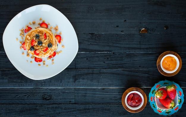 Selbst gemachte pfannkuchen mit frischen beeren, erdbeeren, blaubeeren und ahornsirup auf einem dunklen holz