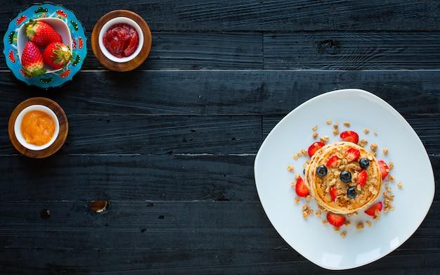 Selbst gemachte pfannkuchen mit frischen beeren, erdbeeren, blaubeeren und ahornsirup auf einer dunklen holzoberfläche.