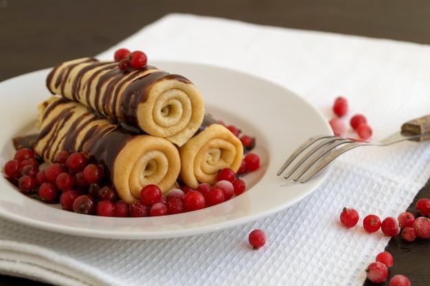 Selbst gemachte pfannkuchen verdrehten sich mit schokolade auf einer weißen platte.