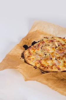 Selbst gemachte pizza auf dem pergamentpapier lokalisiert auf weißem hintergrund