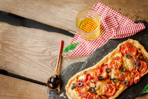 Selbst gemachte pizza auf einem hölzernen hintergrund