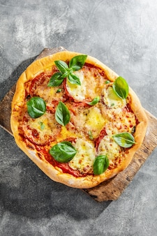 Selbst gemachte pizza mit mozzarella auf grauem hintergrund