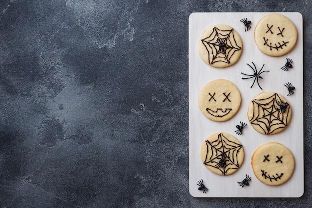 Selbst gemachte plätzchen für halloween, plätzchen mit lustigen gesichtern und spinnennetzen