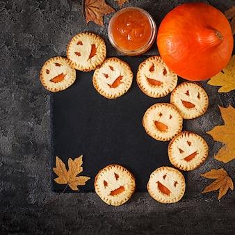 Selbst gemachte plätzchen in der form als halloween-steckfassung-olaternenkürbise auf der dunklen tabelle. ansicht von oben.