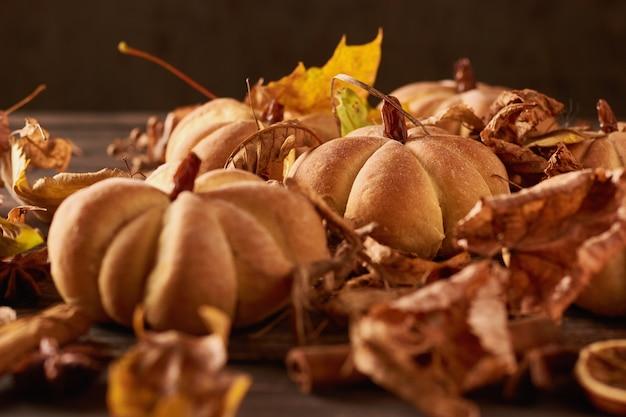 Selbst gemachte plätzchen in form des kürbises im herbstlaub. halloween handgemachte kekse