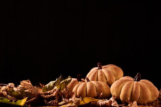 Selbst gemachte plätzchen in form des kürbises im herbstlaub. handgemachte plätzchen halloweens im hintergrund mit copyspace