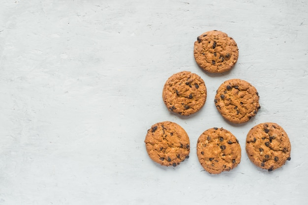 Selbst gemachte plätzchen mit schokolade auf einer grauen tabelle. chocolate chip cookie erschossen