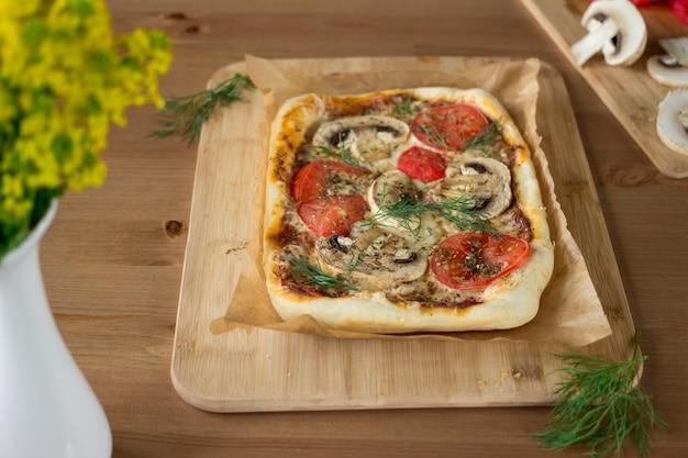 Selbst gemachte rechteckige pizza margherita mit pilzen auf einem hölzernen brett