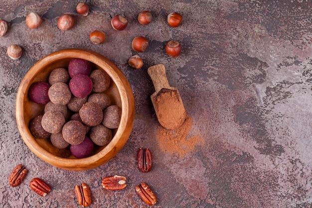Selbst gemachte rohe kakaobälle des strengen vegetariers in der hölzernen schüssel