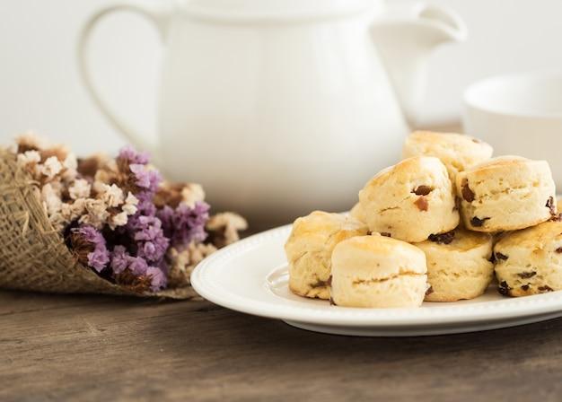 Selbst gemachte rosinen scones dienten mit topf tee auf hölzerner tabelle. traditionelles englisches gebäck.