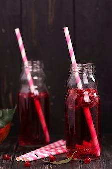 Selbst gemachte rote granatapfellimonade in den kleinen glasflaschen