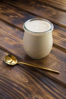 Selbst gemachte ryazhenka im glas auf dem braunen hölzernen hintergrund. fermentiertes milchprodukt. lage vertikal.