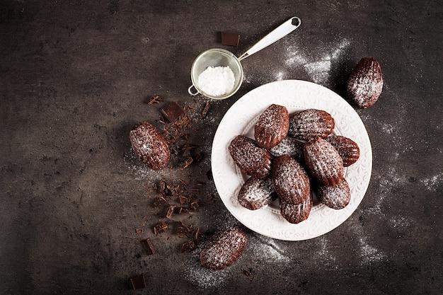 Selbst gemachte schokolade madeleines auf dunkler tabelle
