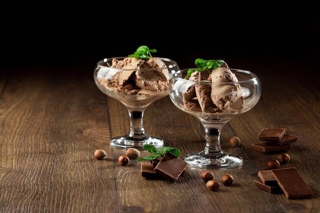 Selbst gemachte schokoladeneiscreme mit den tadellosen blättern, besprüht mit schokolade in einer glasschüssel auf einem holztisch