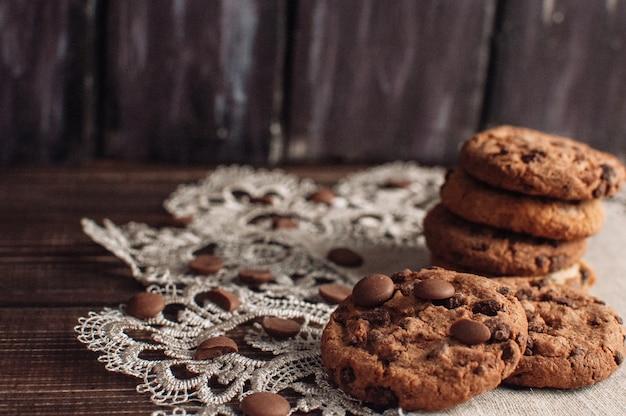 Selbst gemachte schokoladenkekse und zerquetschte schokoladenkrume auf dunkler rustikaler tabelle.