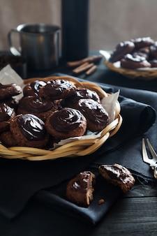 Selbst gemachte schokoladenplätzchen mit tee auf dunkler tabelle