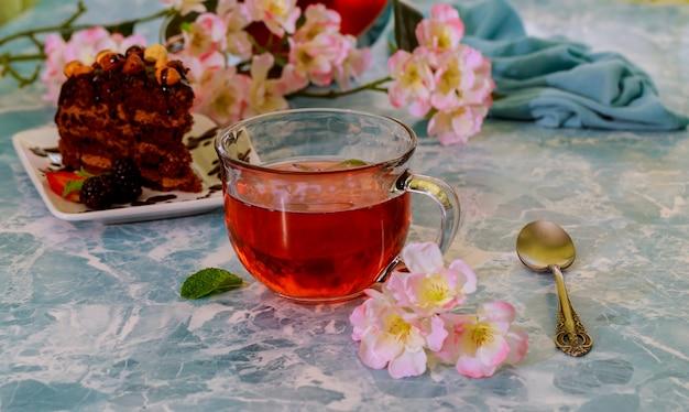 Selbst gemachte schokoladenschokoladenkuchen und tasse tee auf marmorhintergrund, selektiver fokus