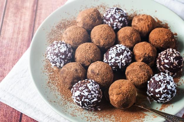 Selbst gemachte schokoladentrüffeln mit kakao und kokosnuss auf der platte