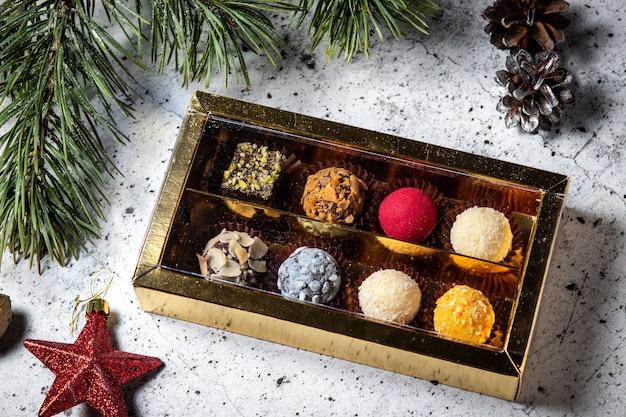 Selbst gemachte schokoladentrüffelsüßigkeiten in einer geschenkbox. zusammenstellung der runden farbigen süßigkeiten