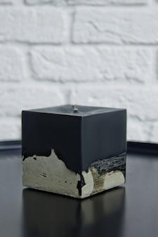 Selbst gemachte schwarze kerze mit beton auf der oberfläche einer weißen wand