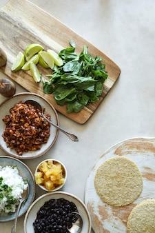 Selbst gemachte tacobestandteile des strengen vegetariers auf dem tisch