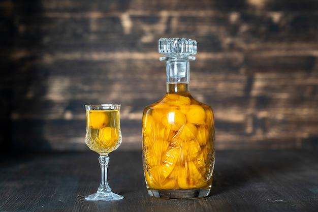 Selbst gemachte tinktur der gelben kirschpflaume in einer kristallflasche und im weinglas auf hölzernem hintergrund, ukraine, nah oben. beerenalkoholisches getränkekonzept