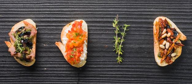 Selbst gemachte toastsandwiche mit thymian auf hölzernem schwarzem hintergrund