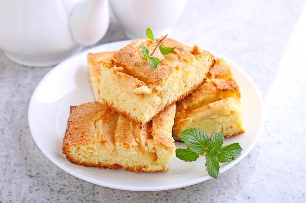 Selbst gemachte torte mit äpfeln und zimt ist geschnittene scheiben auf einer platte, hölzerner hintergrund