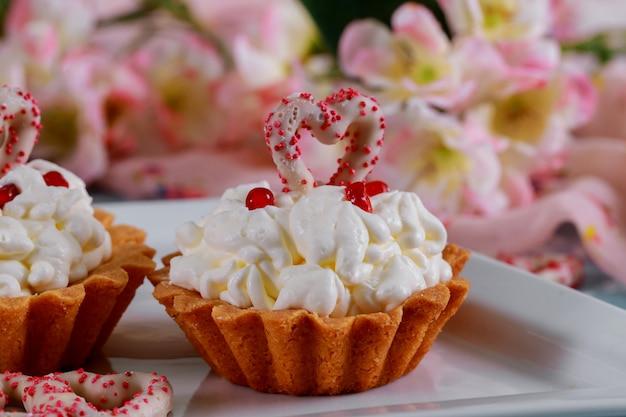 Selbst gemachte valentinsgrußkleine kuchen mit roten zuckerherzen und rosa blumenhintergrund