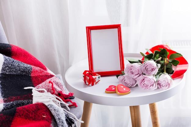 Selbst gemachte valentinstagherzplätzchen, rosa rosen und roter rahmen auf weißer tabelle mit stuhl und rotem plaid