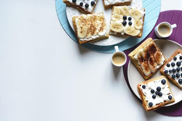 Selbst gemachte waffeln der blaubeere und der banane mit kaffee
