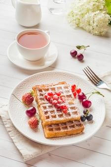 Selbst gemachte waffeln mit sommerbeeren auf einer platte. eine tasse tee auf einem leuchtpult. tiefenschärfe.
