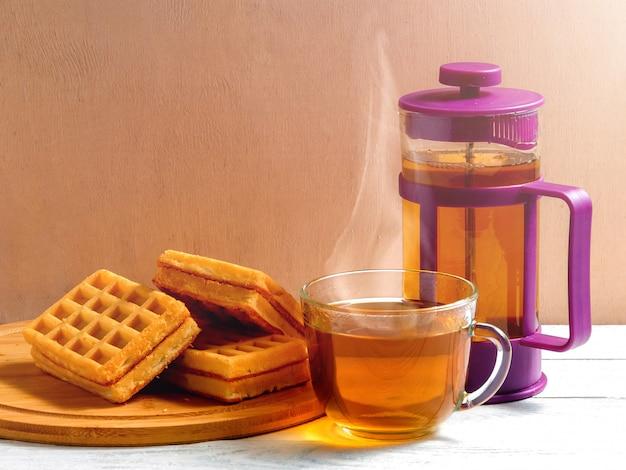 Selbst gemachte waffeln mit stau auf altem holztisch. oblaten mit tasse tee und teekanne.
