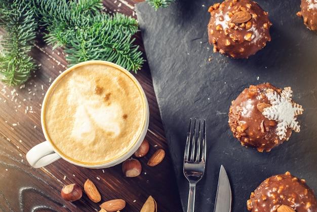 Selbst gemachte weihnachts- oder neujahrsfeiertagsschokoladenschokoladenkuchen mit nüssen auf hölzernem hintergrund. festliche desserts