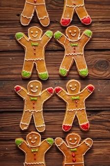 Selbst gemachte weihnachtslebkuchenmänner mit zuckergussmuster auf brauner holzoberfläche