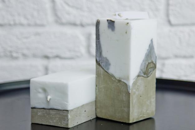 Selbst gemachte weiße kerze mit beton auf der oberfläche einer weißen wand