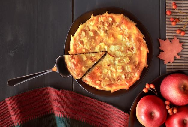 Selbst gemachter apfelkuchen auf dunklem teller mit äpfeln auf dunkler wand