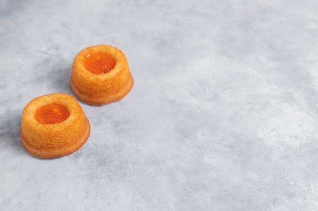 Selbst gemachter aprikosenmarmeladen-fingerabdruck-keks, der auf marmorhintergrund gelegt wird.