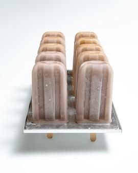 Selbst gemachter bio-schokoladeneislutscher in plastikformen mit einer reflexion von schatten auf einem weißen hintergrund mit kopienraum.