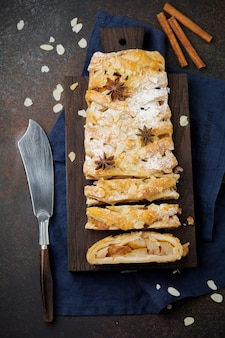 Selbst gemachter birnenstrudel, verziert mit mandeln, anis und puderzucker auf einem rustikalen hintergrund.