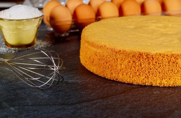 Selbst gemachter biskuitkuchen auf schwarzem hintergrund mit eiern, mehl und schneebesen