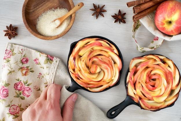 Selbst gemachter blätterteig mit den rosafarbenen geformten apfelscheiben, die in den eisenbratpfannen gebacken werden