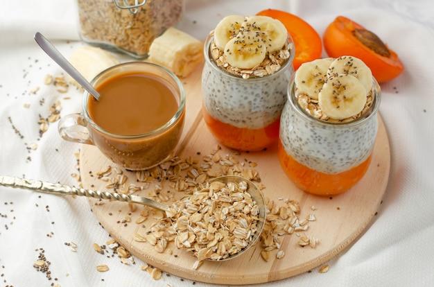 Selbst gemachter chia samenpudding mit banane, zertrümmerten frischen aprikosen- und hafermahlzeiten und kaffee auf hölzernem brett mit kopienraum.