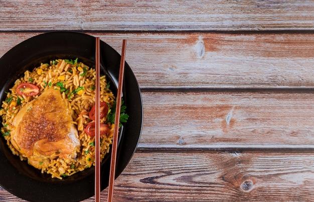 Selbst gemachter chinesischer gebratener reis mit huhn auf einer platte mit essstäbchen in den teller